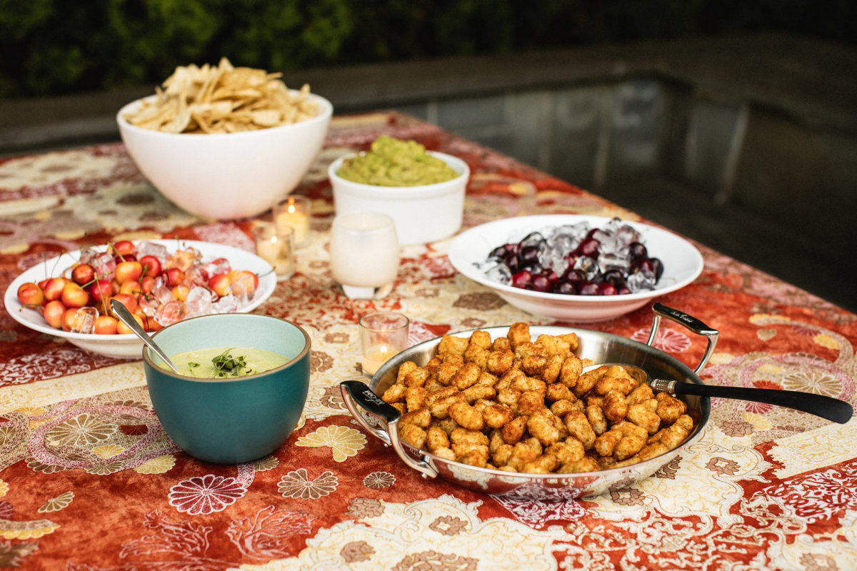 A table filled with some comfort food favorites like guacamole and tater tots.